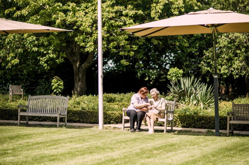Carer and resident sat on a bench