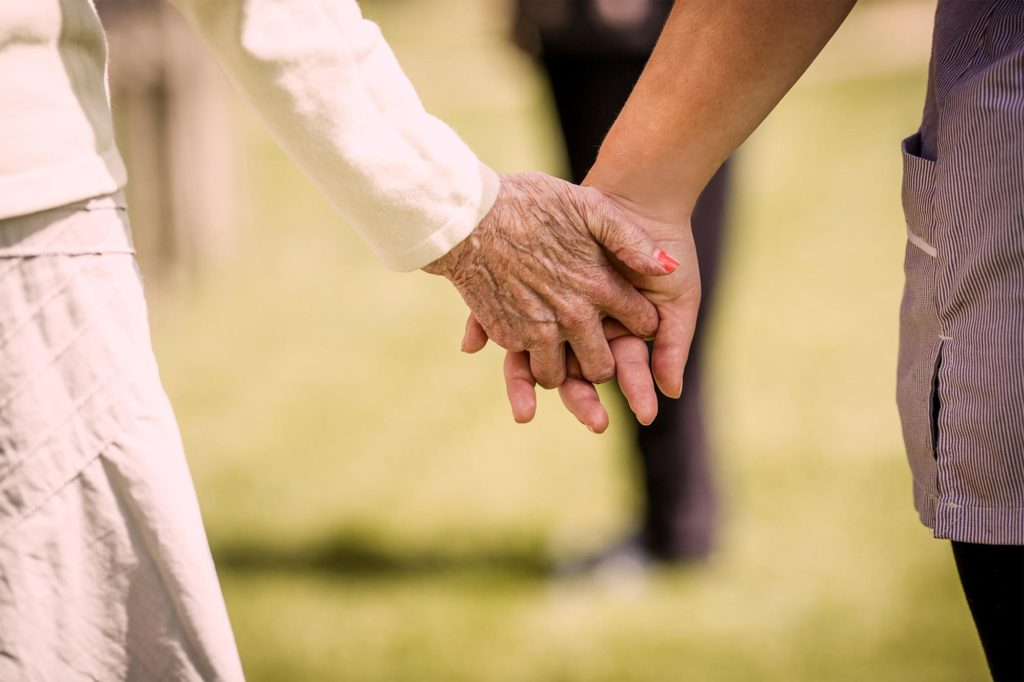 Carer and resident holding hands