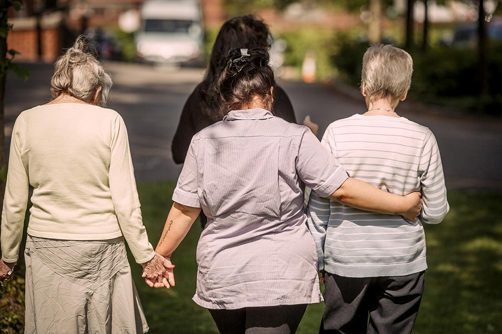A carer and two residents walking