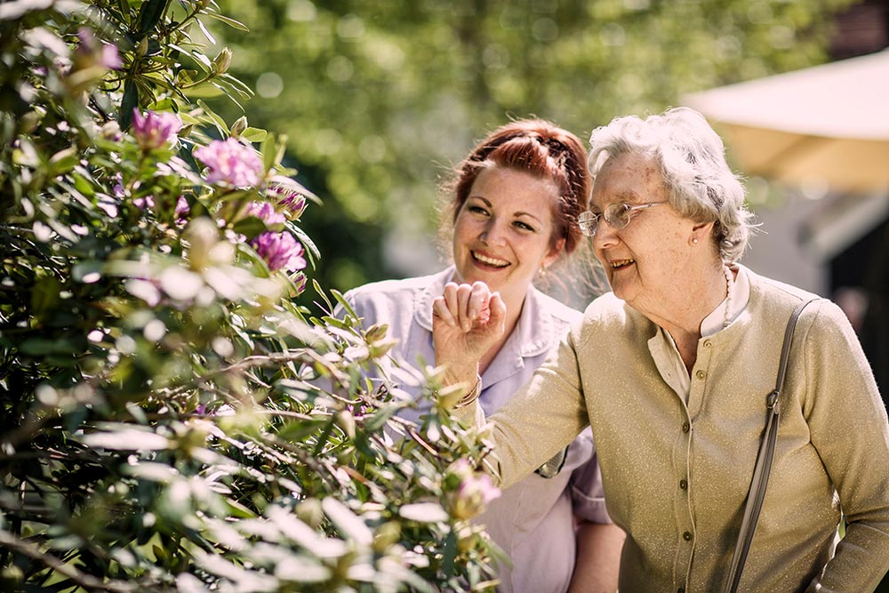 A carer and resident looking at the flowers