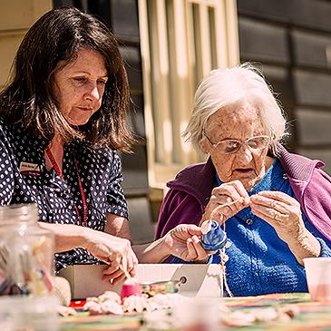 A member of the team doing crafts with a resident